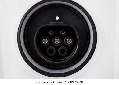 Straight on view of round receptacle for electric car power receptacle outline on white surface