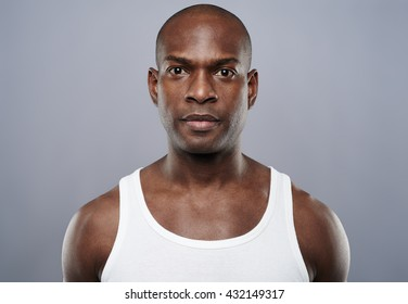 Straight on view of young single handsome African man with calm expression in white sleeveless undershirt