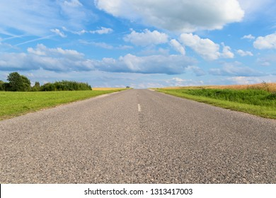 Straight road extending beyond the horizon to a beautiful blue sky with ornate clouds.