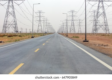Straight road flanked on both sides with high voltage power lines in black and white
