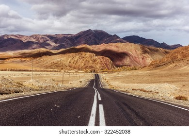 Straight road goes to horizon on mountains backdrop. Altay mountains, Siberia, Russia.