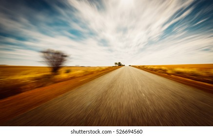 Straight road goes to horizon on background of ble sky and Golden wheat field.  motion blur effect .