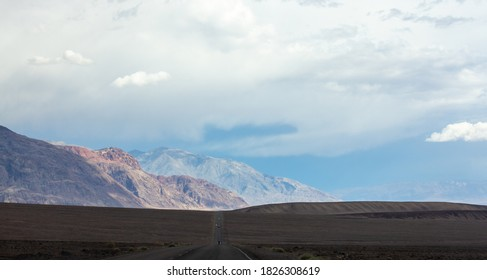 Straight road going up and down on hill with mountains in the background. Landscape of Death Valley National Park, California, USA. Great for background