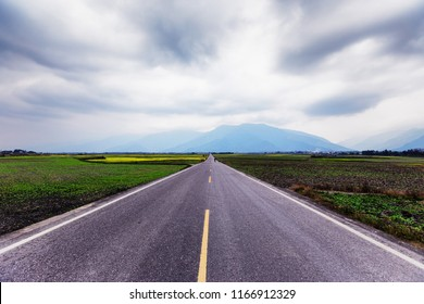 A straight road leading into the distance. This image was taken in a countryside of Taiwan. A straight road represents journey, direction, future, forward and travel. It is suitable for background.