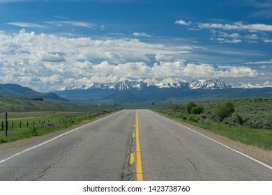 A straight road leading towards the Rocky Mountains