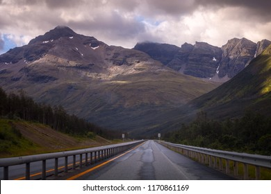 Straight road to mountains in Norway. Toned photo