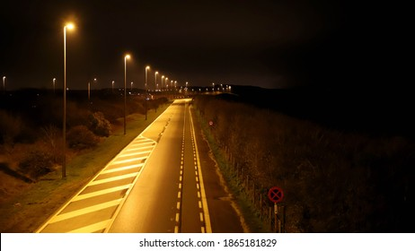 Straight road in the north of Belgian Flanders. Large street lights cast a yellow light on the road. Night photo. An illuminated city is visible in the background. Way of communication.