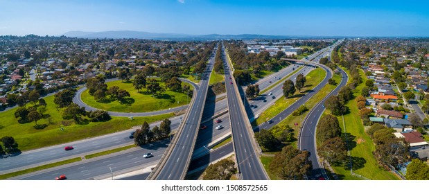 Straight road passing through interchange and leading to mountains in the distance. Aerial view in Melbourne, Australia