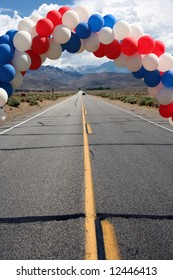Straight road with patriotic balloons leading to a party in the mountains