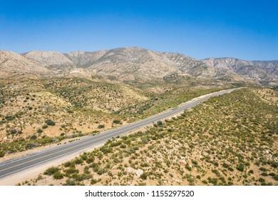 Straight road through California desert wilderness in the Mojave.