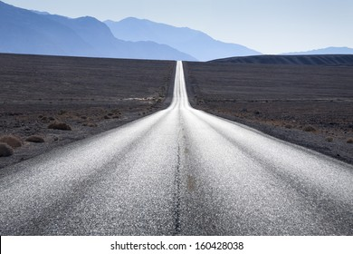 Straight road towards mountain range in horizon at Death Valley, USA