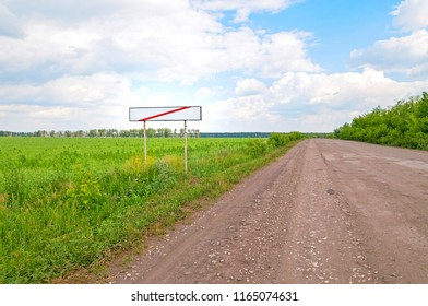 Straight road and white empty sign with red line on roadside at town gates against against  sunny meadow background. Bolshaya Doroga village, Tambovsky region, Russia.