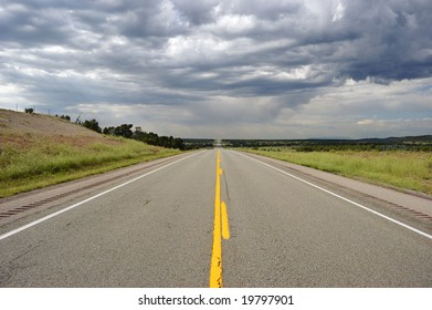 Straight road with yellow mid-line and dramatic clouds