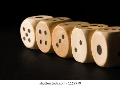 Straight row of wooden dice lit by the sun on a black background.