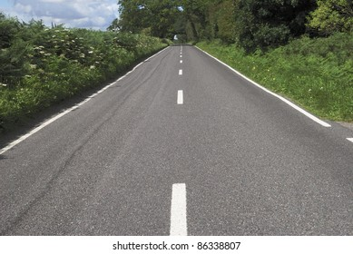 Straight tarmac country road with white lines on edge of woodland in West Sussex. England