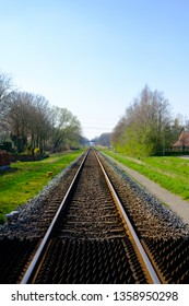 Straight traintrack with grass and trees on the side.
