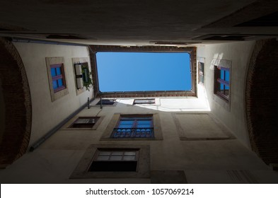 Straight up view of the blue sky from under an ancient archway. Alfama disctrict, the most famous and ancient typical neighborhood of Lisbon. Portugal.