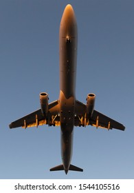 Straight up view of narrow body (single aisle) aircraft passing overhead about to land illuminated by sunset light. Wide angle lens used.