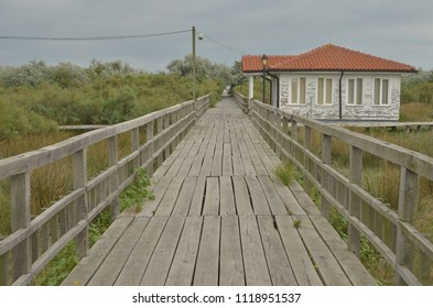 Straight view on elevated wooden pedestrian walkway and wooden house nearby. Non-urban summer scene. Solitude.