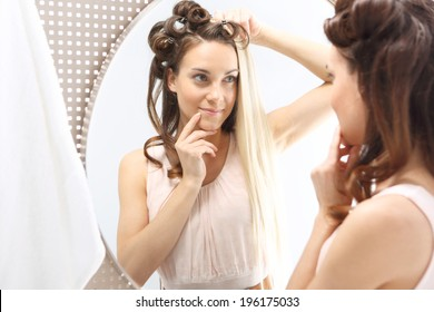Straight or curly?  Woman with hair standing in front of a mirror. Changing hair color. Full colored hair.