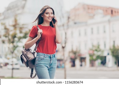 Straight-haired young beautiful smiling caucasian girl wearing casual red t-shirt and jeans outside, traveling abroad, chatting on cell phone