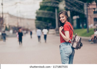 Straight-haired young beautiful smiling girl wearing casual red t-shirt and jeans outside in park, strolling, going for a walk, meeting with friend, half turned
