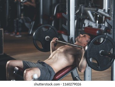 Strained topless male is doing effort while exercising with weights. He is lying on machine bench and doing chest press-up. Be strong and fit concept