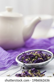 Strainer infuser with loose blue mallow flowers tea on purple cloth with ceramic teapot and cup. - Shutterstock ID 1986062636