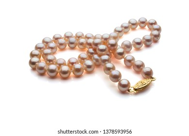 A strand of pink pearls and a gold clasp compose this necklace. Set on a white background.