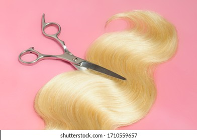 a strand of wavy blonde human hair weaves extensions with a pair of steel scissors