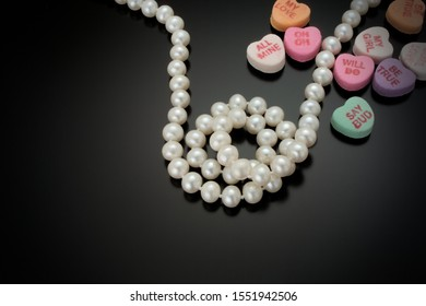 A strand of white round cultured pearls curl in the center of a black reflective background and is surrounded by candy Valentines Day hearts.