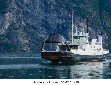 Stranda, Møre og Romsdal, Norway July 25, 2019 Ferry boat coming to the pier on background of norwegian nature and fjord