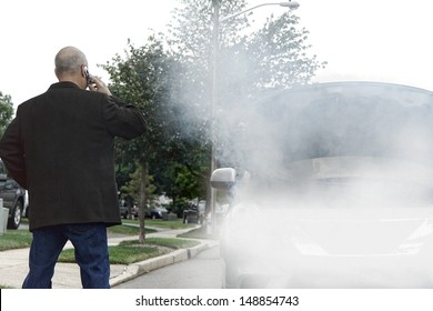 Stranded motorist driver on side of road calling on cell phone for emergency assistance help near broken down car with smoke or steam from hose leak smoking out of open automobile engine compartment