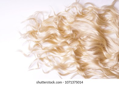 strands of curly light blond hair on white background