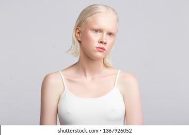 Strange face. Grey-eyed women with white skin wearing white camisole having strange face expression
