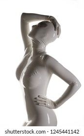 strange fetish woman in mask standing in a white tight rubber latex catsuit on white background isolated
