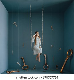 Strange fine art concept of opening your mind. Alice in Wonderland. Girl sitting on a swing with a key in her hand surrounded by many giant keys