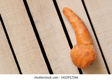 Strange funny homegrown carrot on wooden box background. Ugly food, unusual deformed fruits and vegetables, misshapen produce, food waste problem concept. Top view, copy space.