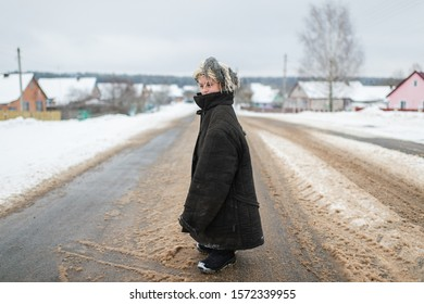 Strange little girl in worn oversized clothes standing at snowy road win winter day in russian village.