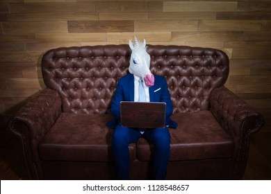 Strange man in elegant suit working at home office. Unusual young manager in comical mask on background of wooden wall. Funny unicorn sits on sofa like a boss.