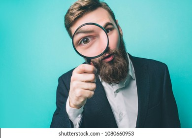 Strange man is looking straight through the loupe. He wonders. Isolated on blue background