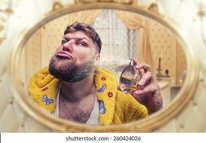 Strange man perfumes himself looking in the mirror