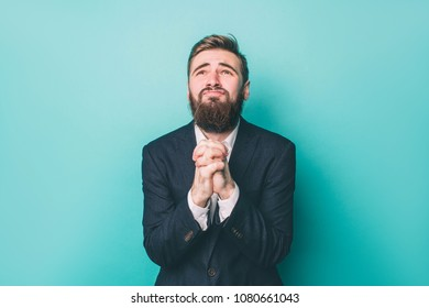 Strange man in suite is holding his hands together ad looking up. He is praying and begging his God. Isolated on blue background