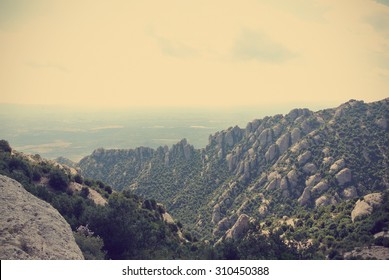 Strange rugged landscape of the Montserrat mountain, in Catalonia, Spain. Image filtered in faded, washed out, retro style with soft focus and dark vignette; nostalgic vintage travel concept.