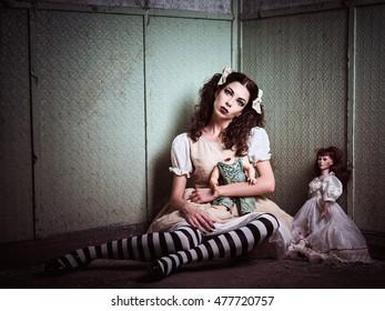 Strange sad girl with dolls sitting in the forsaken place