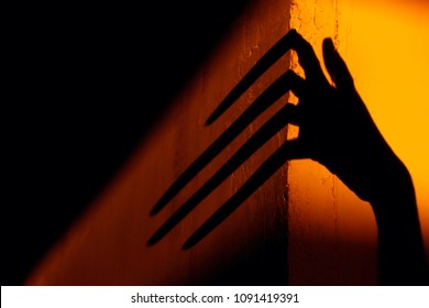 Strange Shadow On The Wall.Terrible Shadow. Abstract Background. Black Shadow Of A Big Hand On The Wall. Silhouette Of A Hand On The Wall. Nightmares. Scary Dreams.