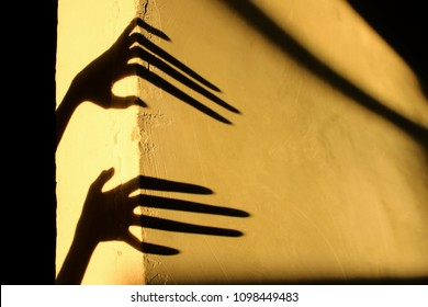 Strange Shadows On The Wall.Terrible Shadows. Abstract Background. Black Shadows Of A Big Hands On The Wall. Silhouette Of A Hands On The Wall. Nightmares. Scary Dreams.