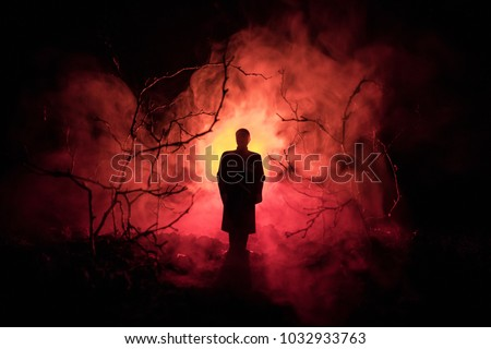 strange silhouette in a dark spooky forest at night, mystical landscape surreal lights with creepy man