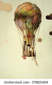 Strange steampunk balloon which flies between clouds and aims for the stars. On light background