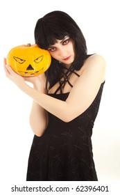 Strange woman in black dress holding a Jack-o'-lantern